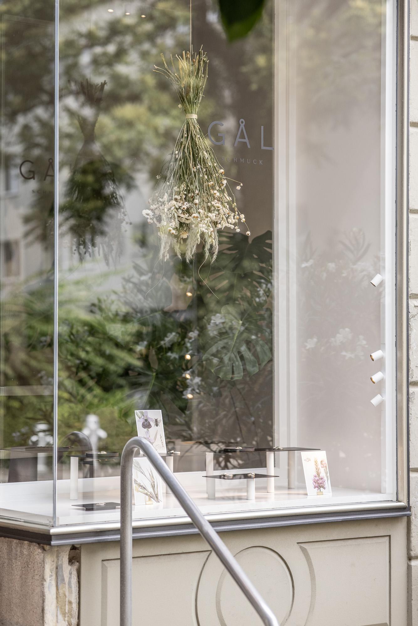 Foto vom Schaufenster des Goldschmiedeateliers mit Schmuckstücken und Trockeblumen ausgestellt