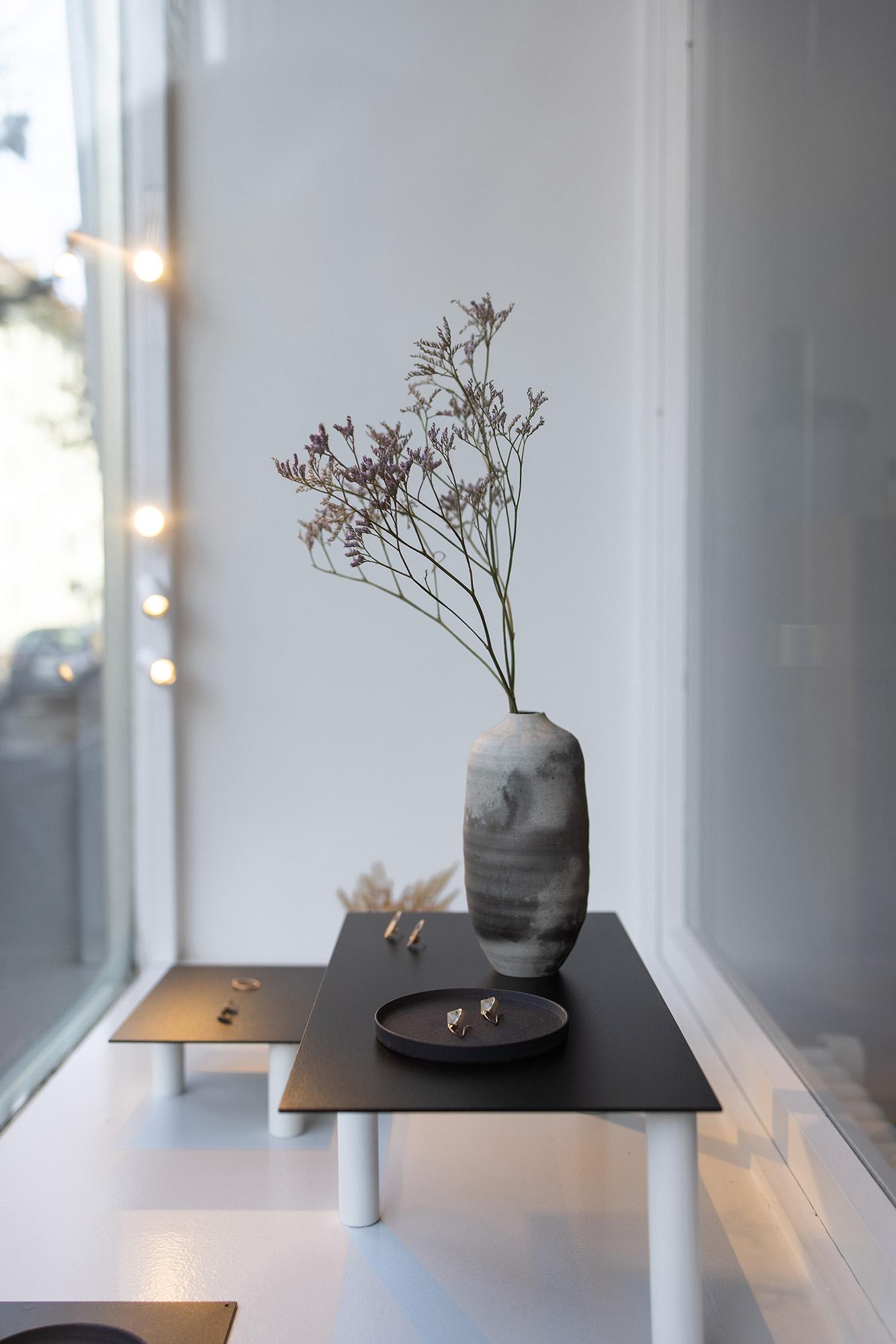 Foto der Schaufenstereinrichtung mit Schmuck und Blumenvasen.
