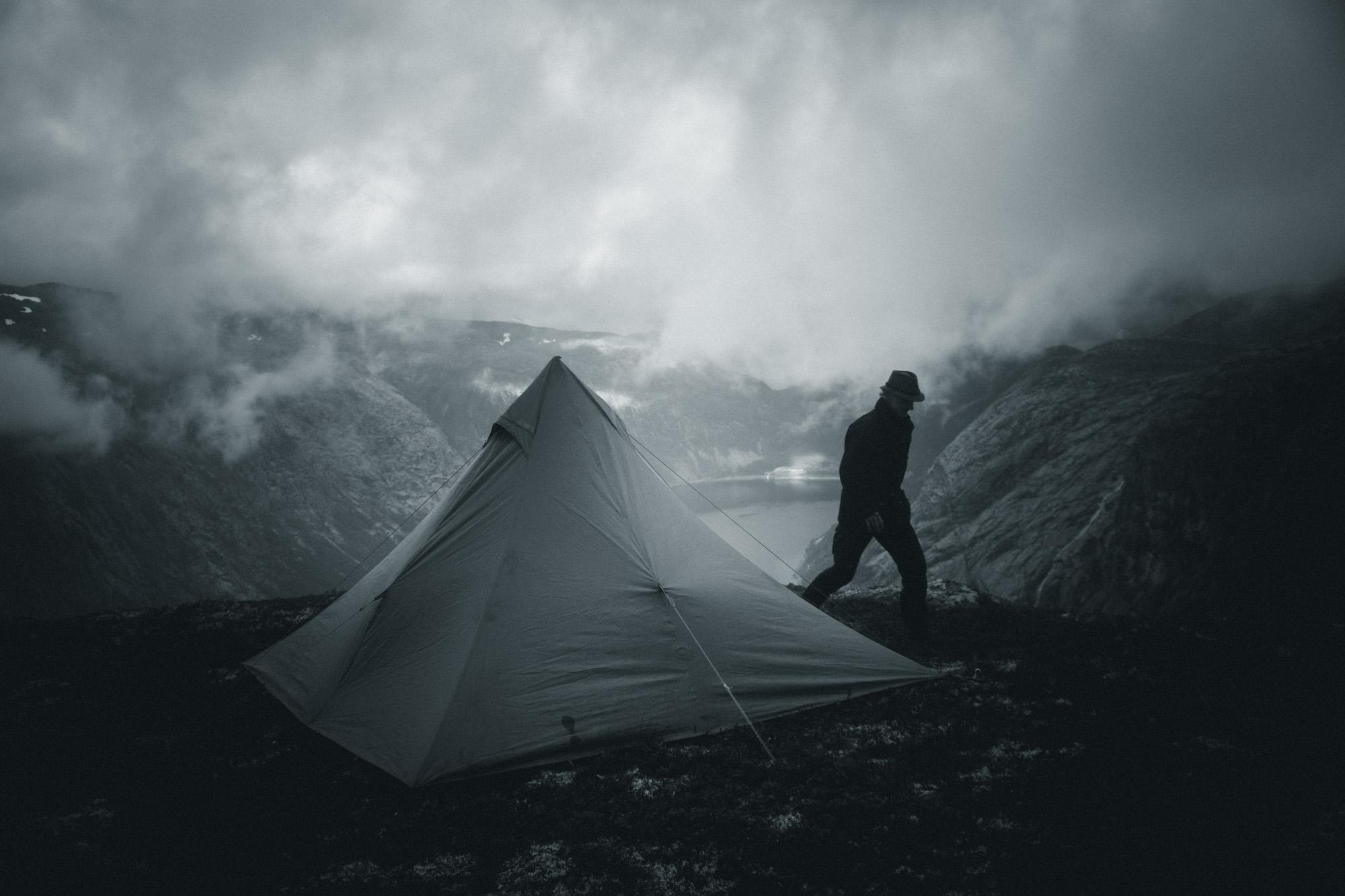 Mann vor Zelt auf Gipfel in Norwegen Schwarzweiß