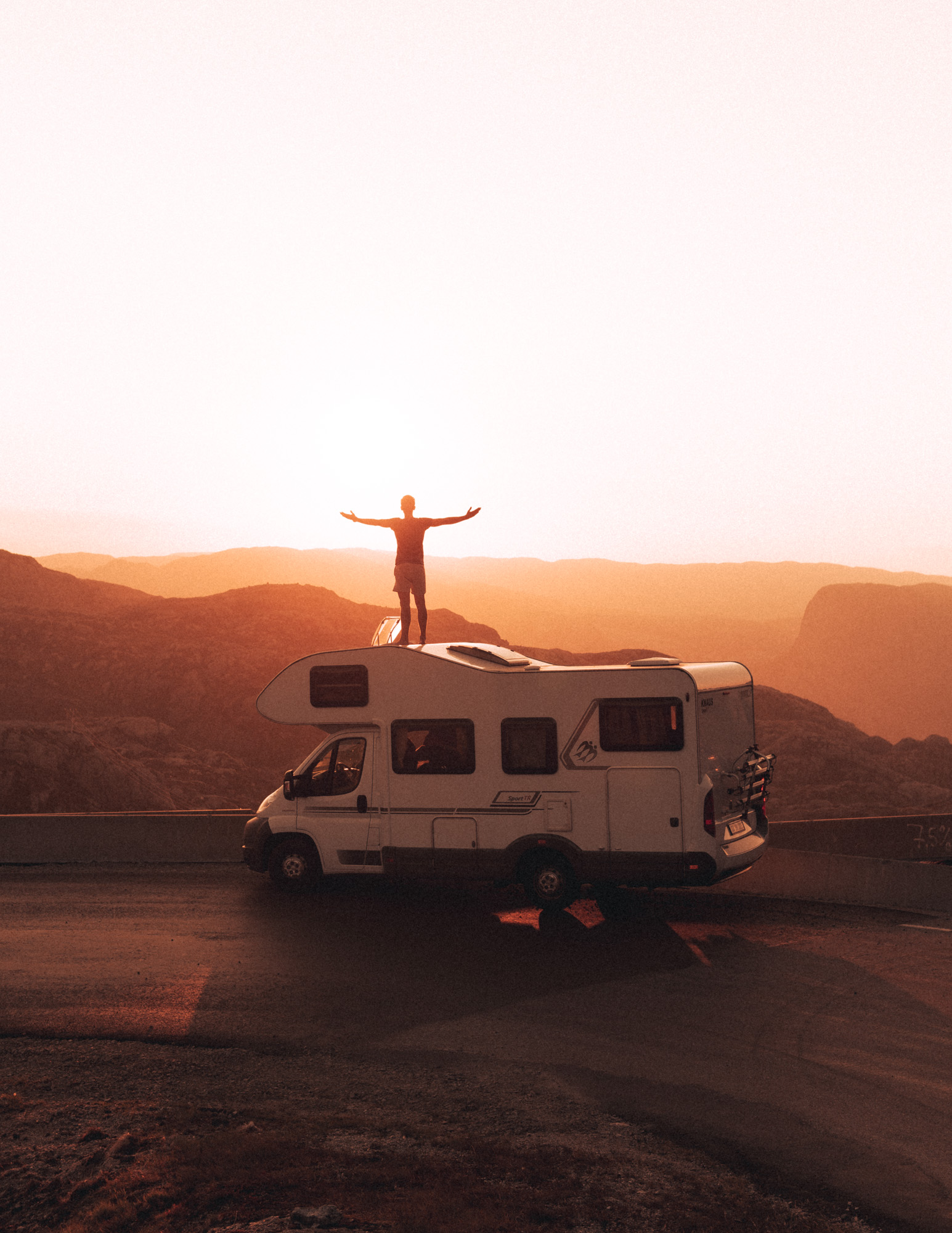Mann steht im Sonnenuntergang auf Wohnmobildach in Norwegen