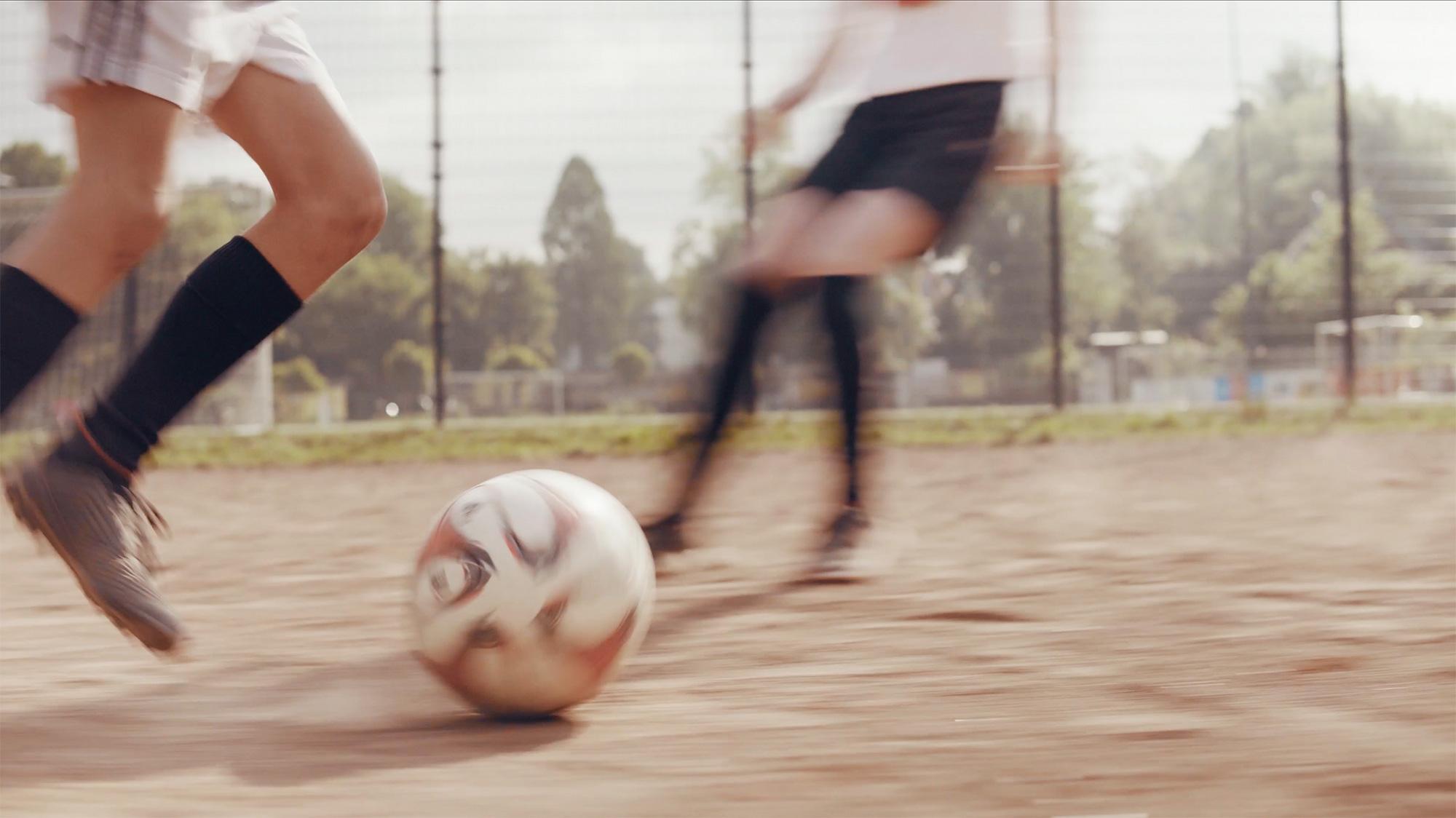 Junge mit Ball am Fuß auf Ascheplatz