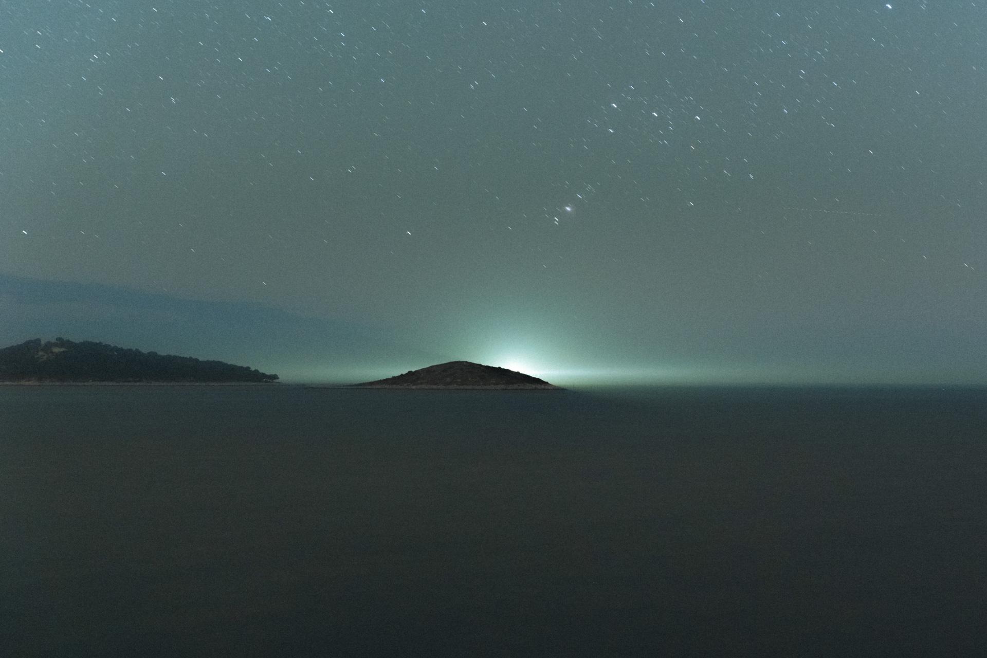 Sternhimmel mit Leuchtturm über dem Meer