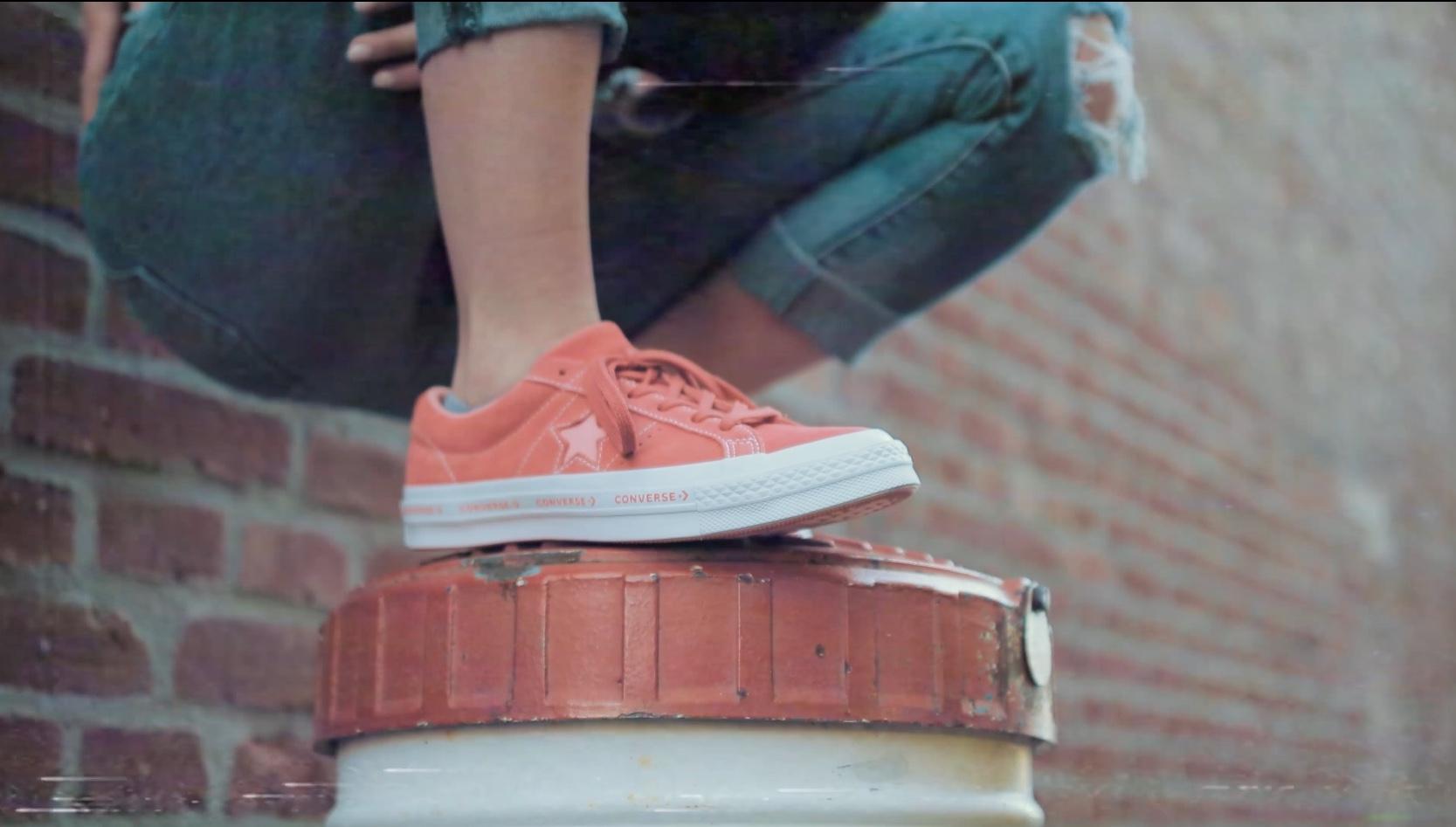 Converse Schuhe vor Backsteinwand