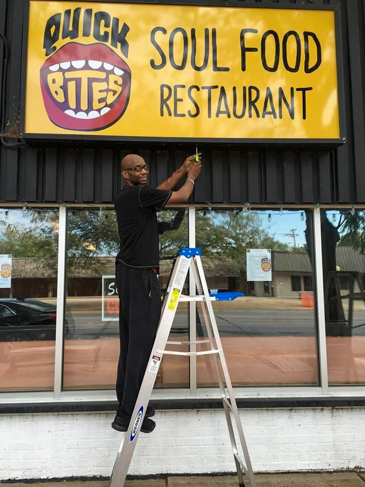Founder, Justin Epting, adjusting the Quick Bites Soul Food outside of the restaurant's store front