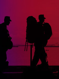 The silhouettes of men in military fatigues carrying supplies.