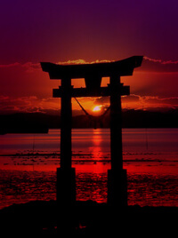 A Japanese torii stands before a lake, the sun setting in the background.