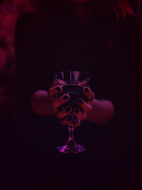 A woman in black robes presenting a chalice of liquid, as though part of a ritual.