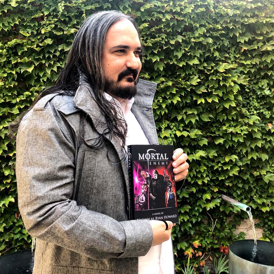 Photo of Nicholas Ryan Howard hooded with his novel