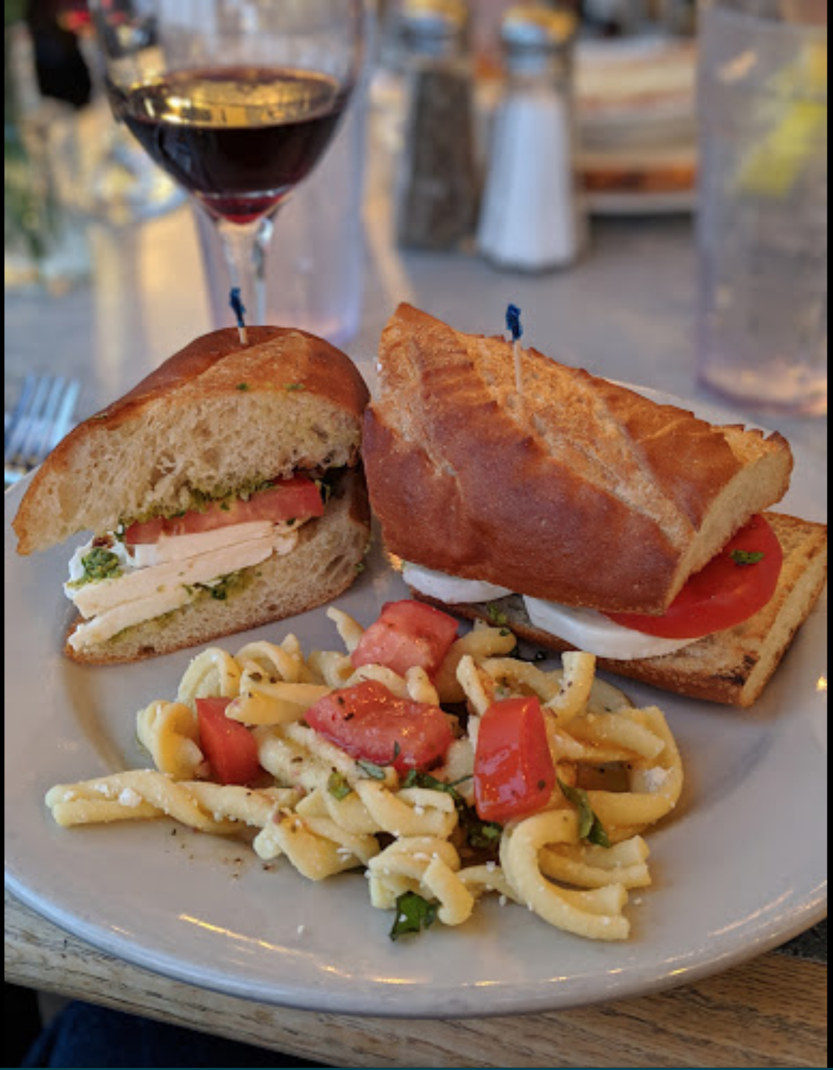 Caprese Sandwich next to a glass of wine and side of pasta.