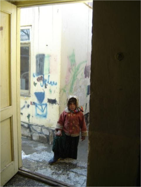 A young girl stands in the doorway looking in.