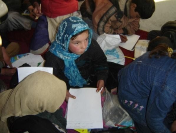 A young girl looks up from her study materials in class.