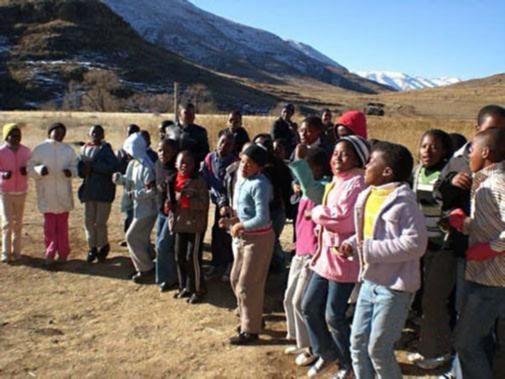 Children in a half circle singing.