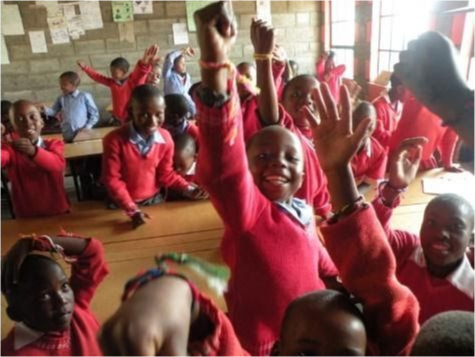 A group of children in class wearing read sweaters raise their hands towards the camera.