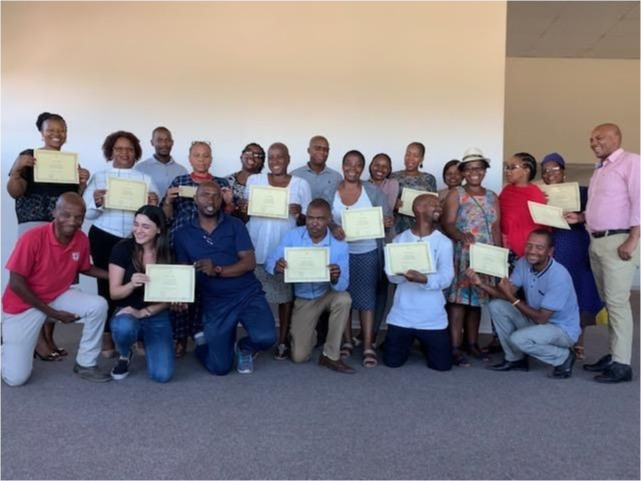 A group of Teachers holding certificates at a Teacher's college.