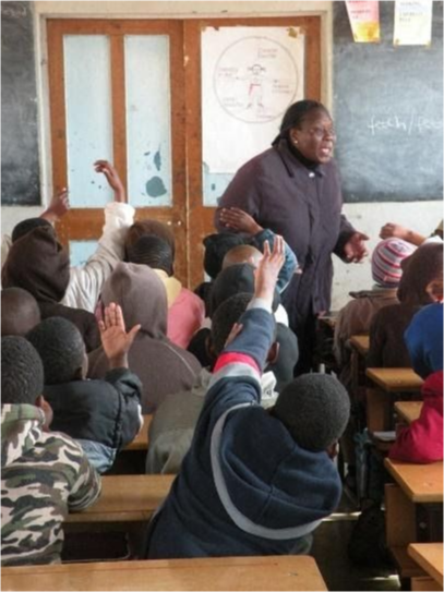 A teacher teaching a class with students actively participating; raising their hands.