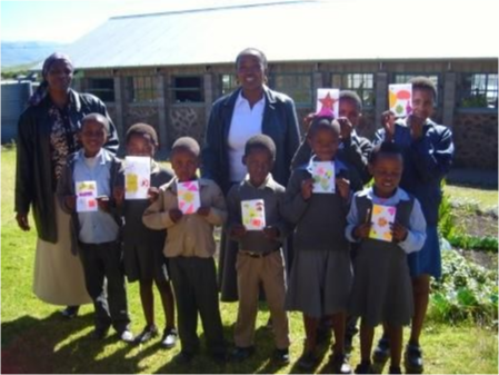 A children's class holding up drawings.