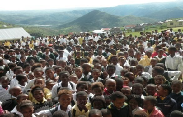 A large group of students gathered in the foreground with rolling hills in the background.