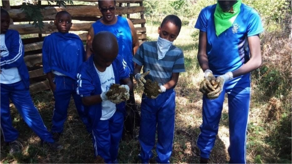 Teachers and students in blue school uniforms hold kindling.
