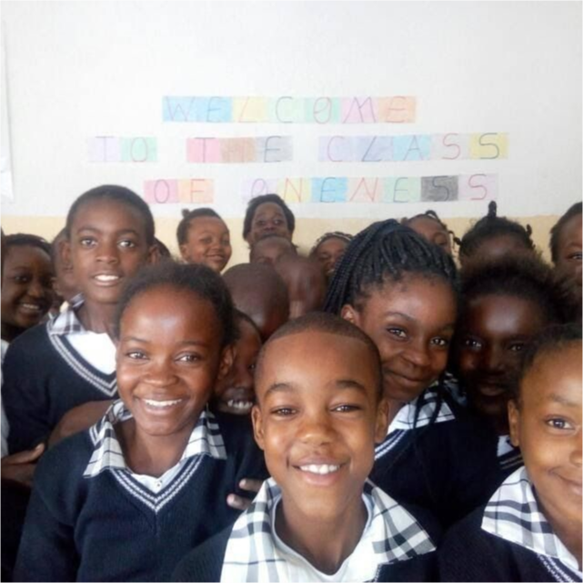 Students in class smile in the foreground with a banner in the background that reads Welcome to the class of oneness.