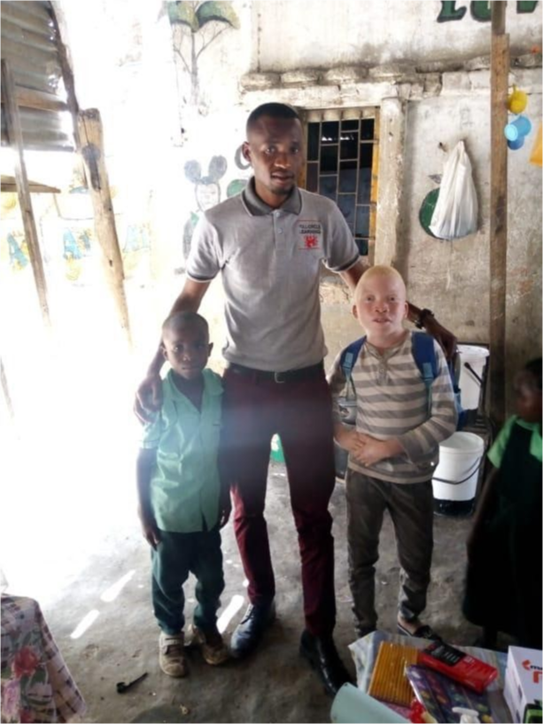 Eric Muleya is joined by two students outside a school.