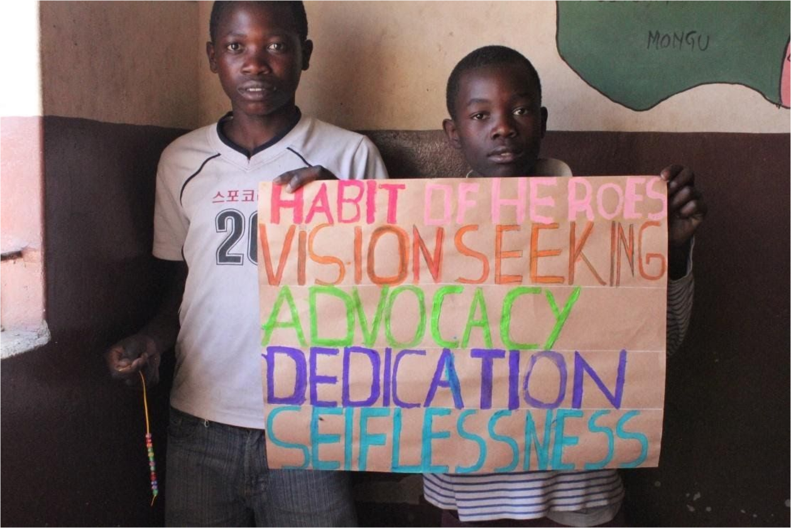 Two boys in class holding a sign that reads Habit of Heroes, Vision Seeking Advocacy Dedication Selflessness