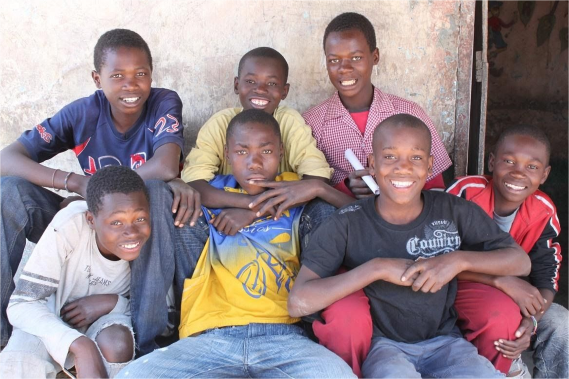 A group of boys outside of a classroom gather for the camera.