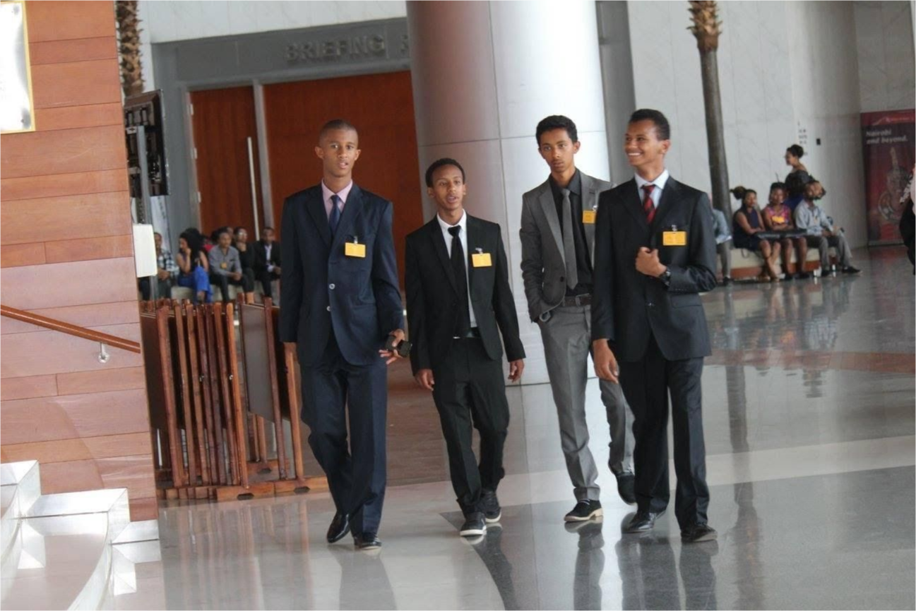Four students in suits at the African Union building.