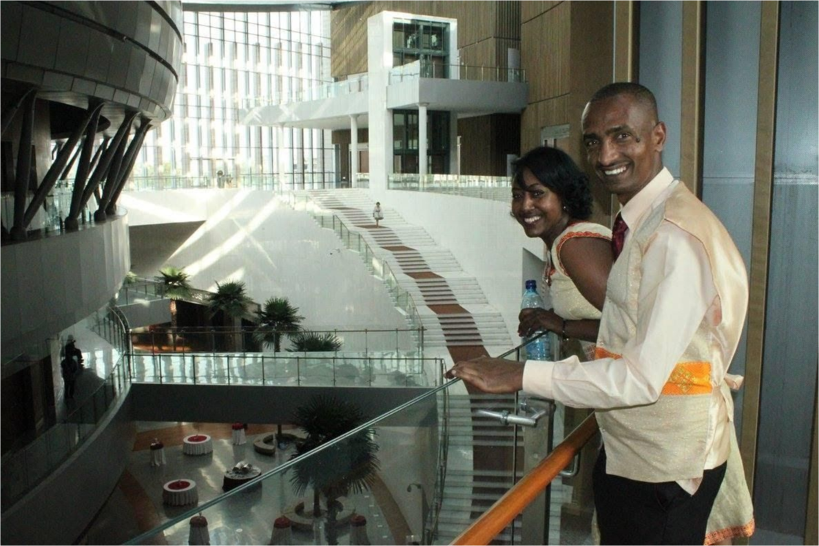 A man and woman smiling at the African Union building.