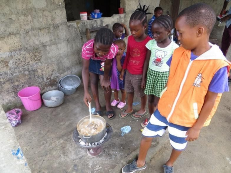 Young students looking down at a pot of soup.
