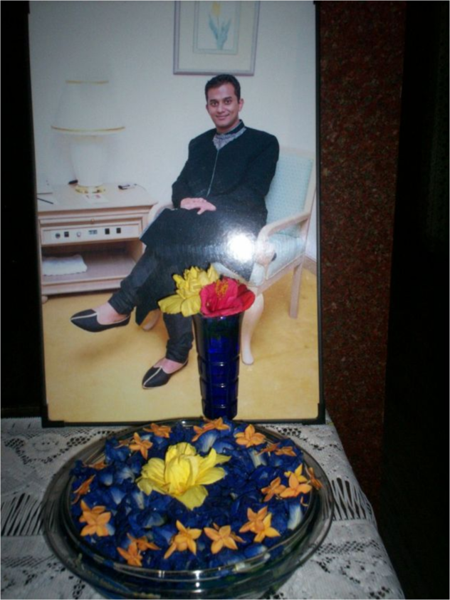 A portrait of Nishanth Selvakumar behind a ceremonial dish.