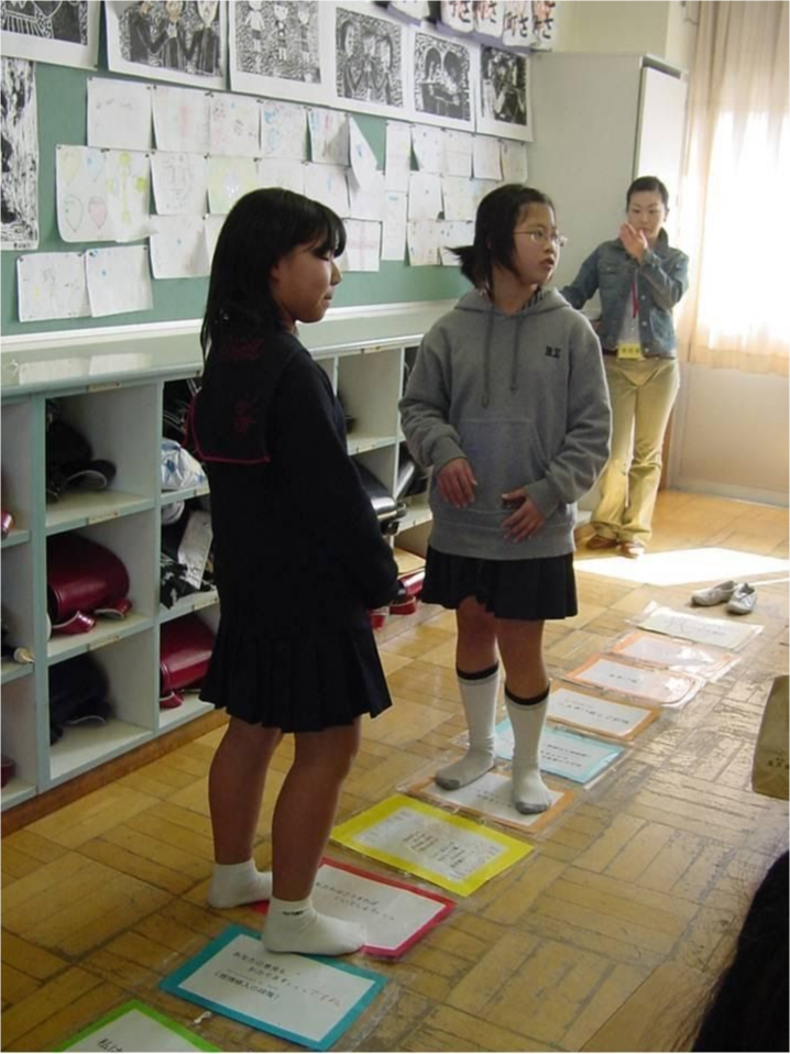 Students in class standing on paper coordinated on the floor