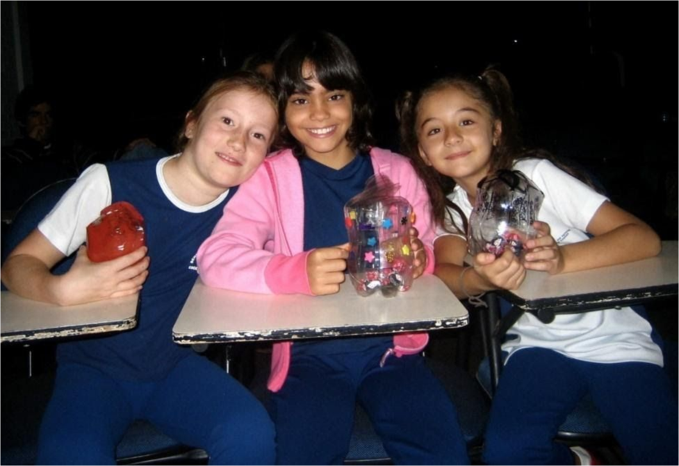 Three young students at their desks smiling together
