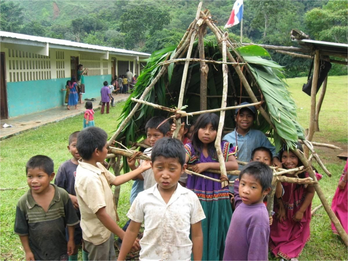 A group of children playing together building an overhang of branches