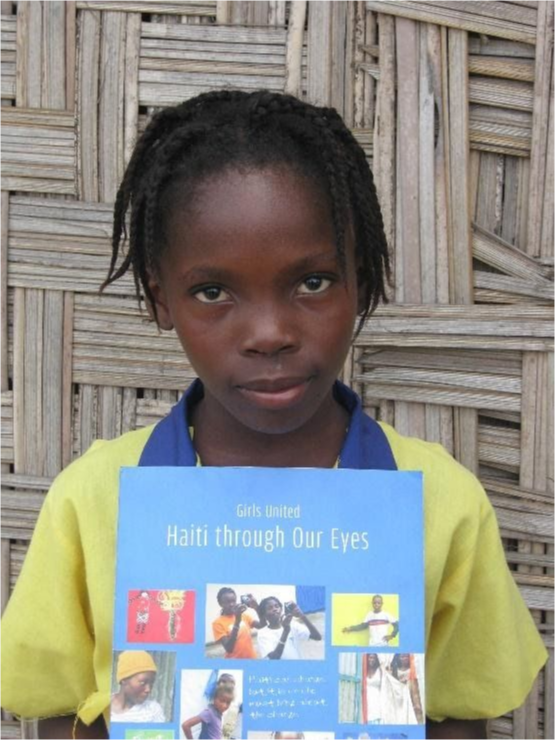 A girl in Liberia holding up her book