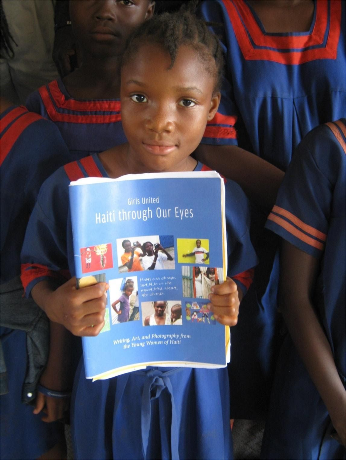 A young girl holding up her book surrounded by her classmates