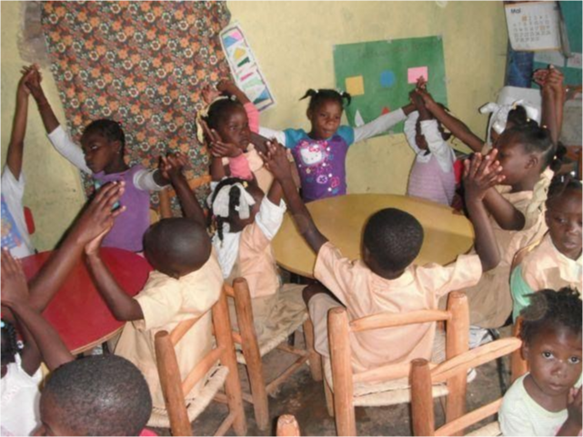 Children in class learning with their hands reached out connecting to each other in a circle