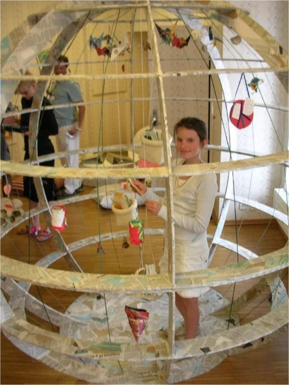 A student stands within her artwork as she works on it.