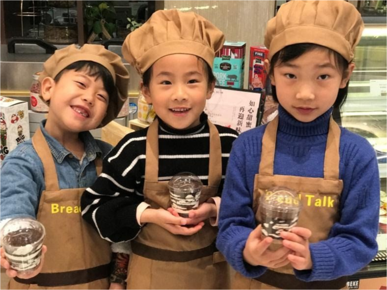 Three young students in chef hats