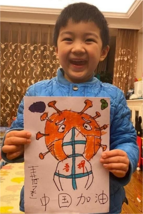 A child smiles with his drawing