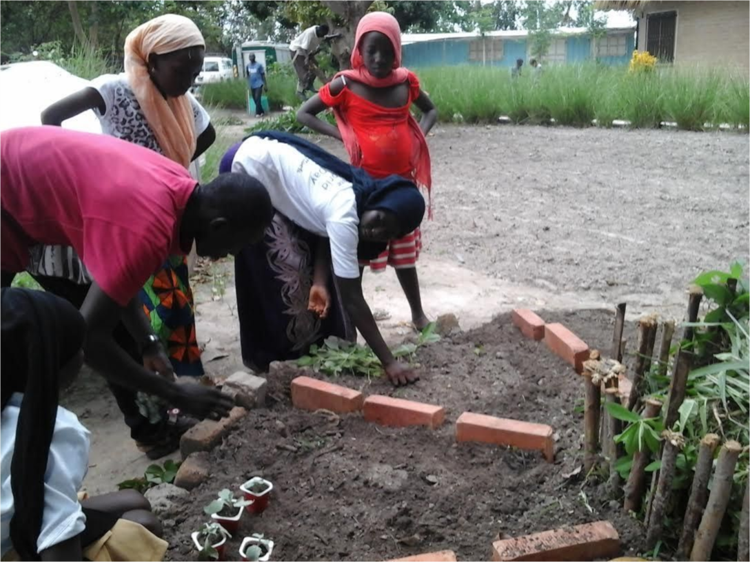 Students laying brick in a formation in a garden