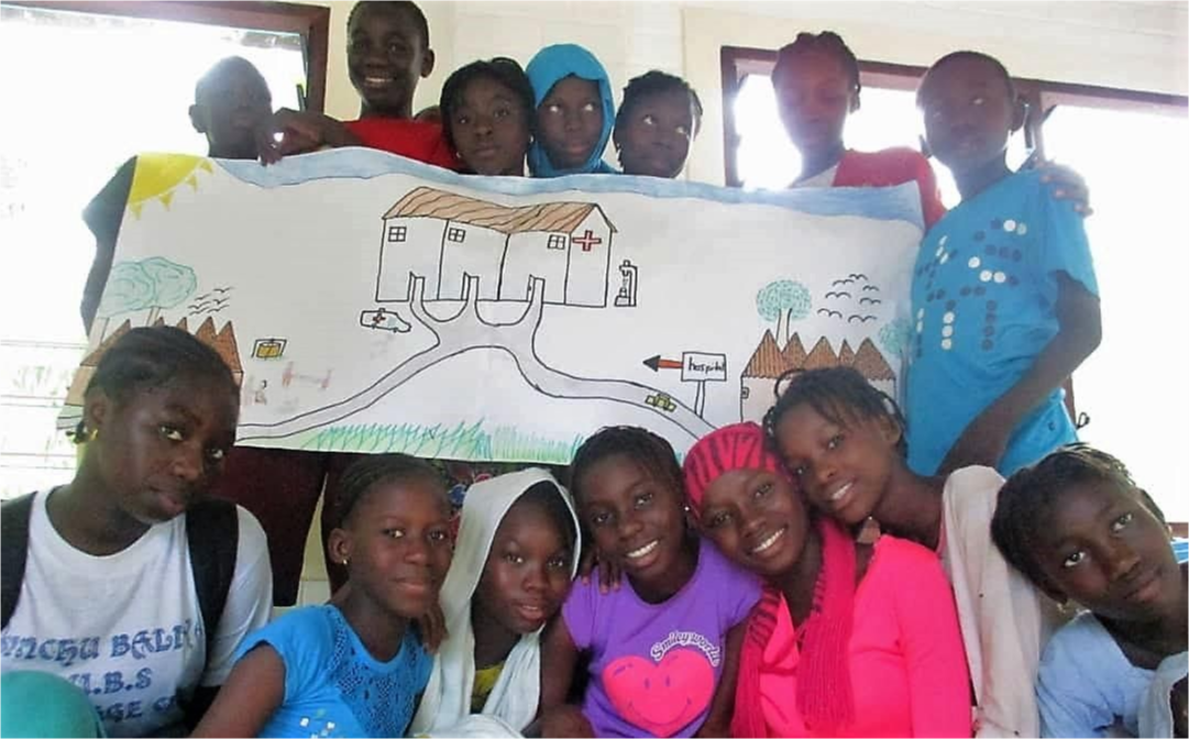 Students gathered holding a banner with a drawing of a building