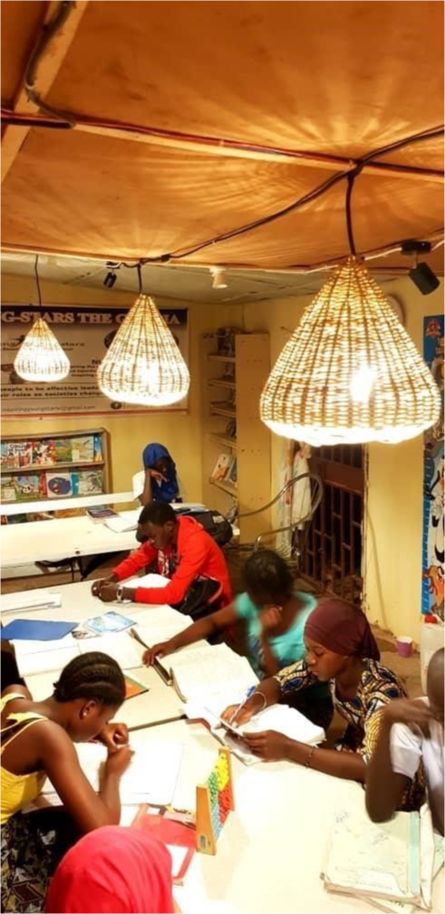 Students at work on a long table lit above by woven straw covered lights