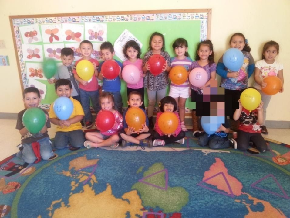 Piru children gathered holding balloons