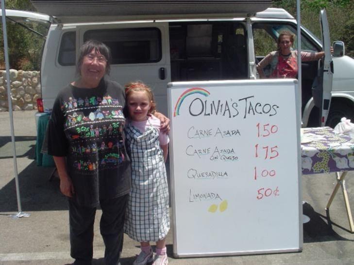 A child next to a sign saying Olivia's Tacos, a menu follows