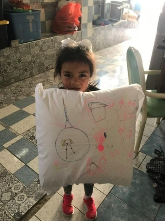 A small child holding a decorated pillow