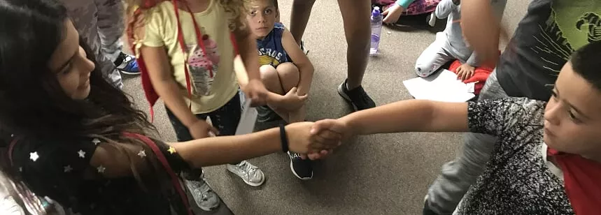 Two children shake hands surrounded by a group.