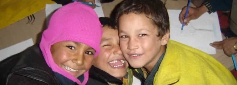 Three children smiling squished together in laughter.