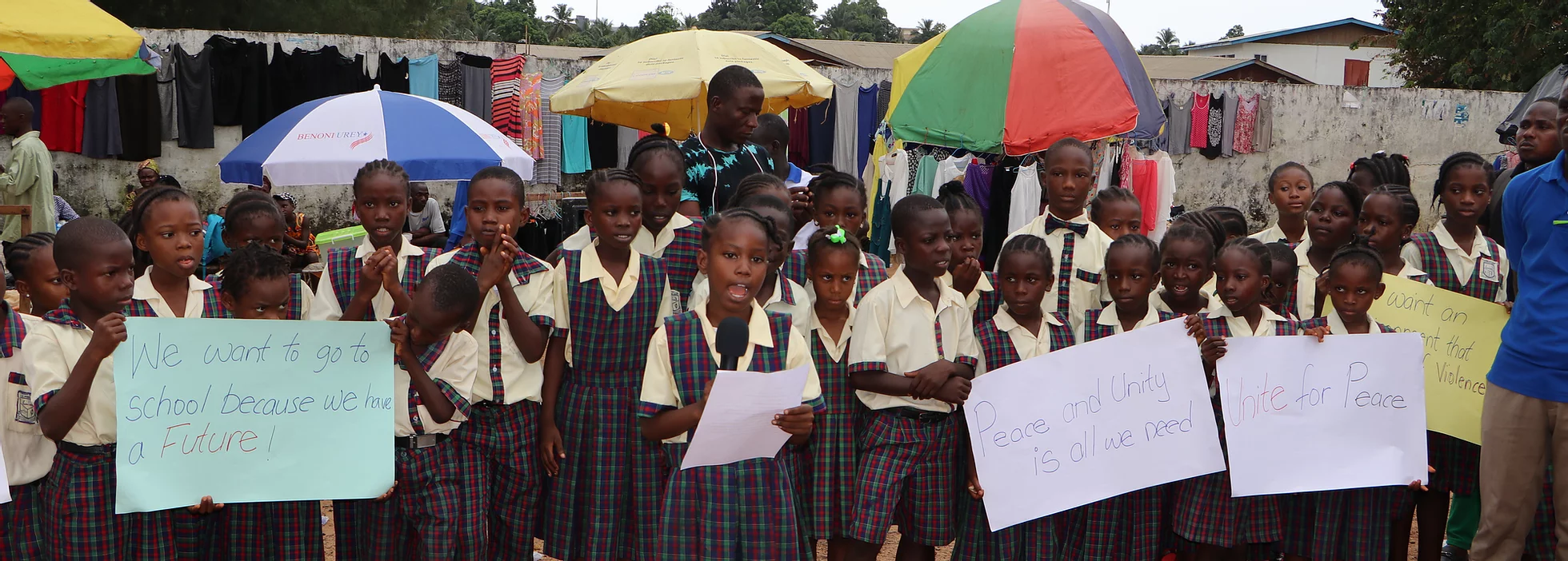 A group of children in Liberia addressing the camera with signs and speaking into the microphone.