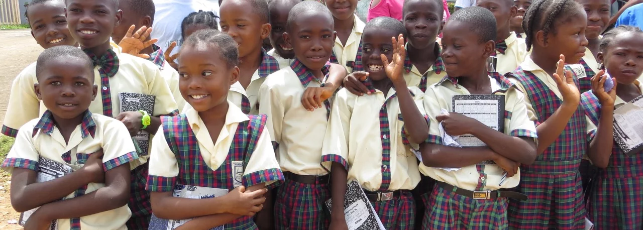 A group of children in school uniform smile and wave.