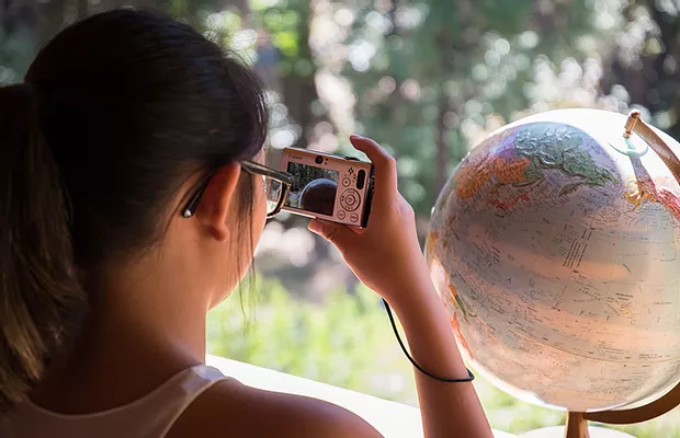 A student takes a picture of a globe on a stand with her camera